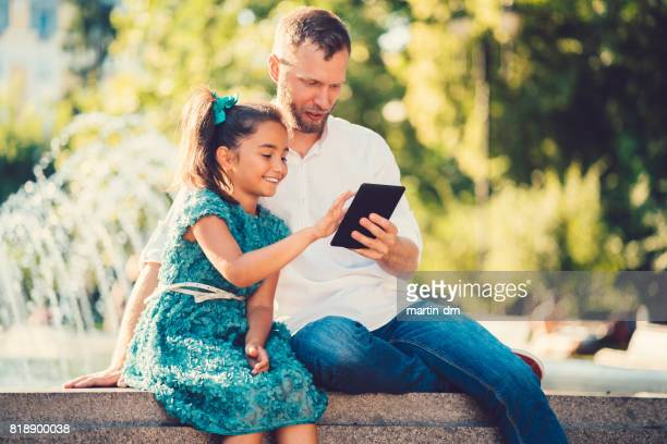 Father and daughter sitting at the fountain and using tablet pc