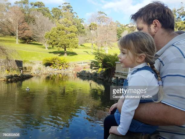 Father And Daughter Sitting By Canal