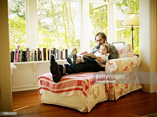 Father and daughter sitting in chair reading book