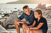 Father and daughter relaxing on a rocky beach by the sea and having time together