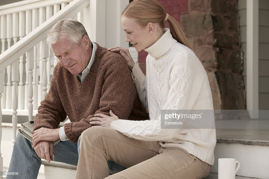 Father and daughter sitting outside on steps