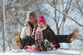 Father and daughter sledding on snow covered hill