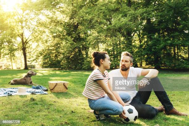 father and daughter spending time together, sitting with soccer ball in park