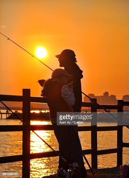 Father And Daughter Standing By Railing On Pier Against Sky During Sunset