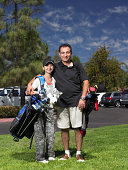 Father and daughter (13-14 years) standing on golf course, portrait