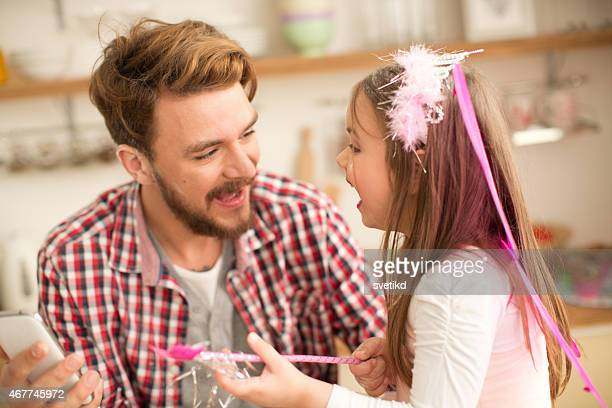 Father and daughter talking in kitchen.