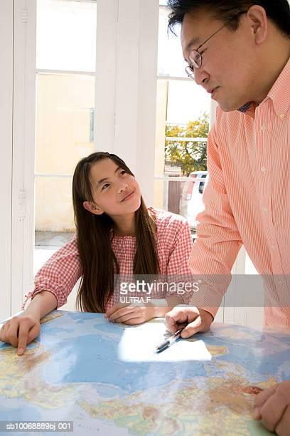Father and daughter talking over world map