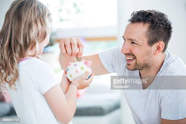 Father and daughter throwing coin into piggy bank