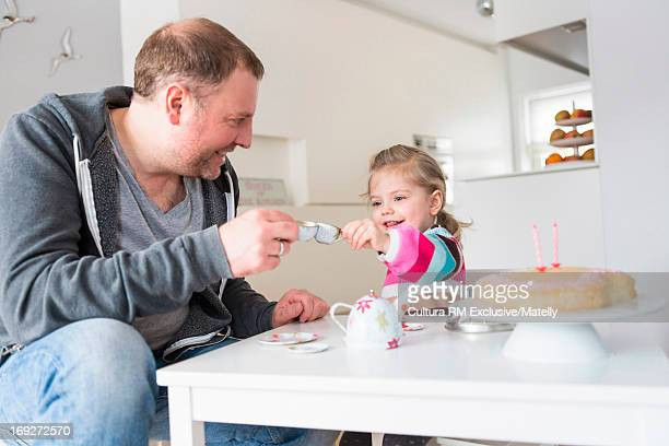 Father and daughter toasting at tea party with cake