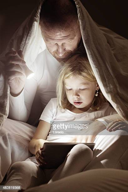 Father and daughter using a tablet device at bedtime