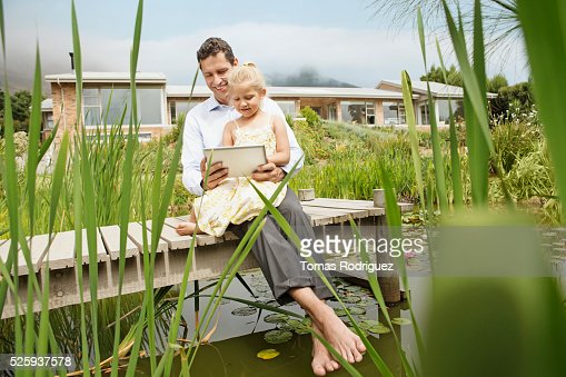 Father and daughter using digital tablet (4-5) outdoors : Bildbanksbilder