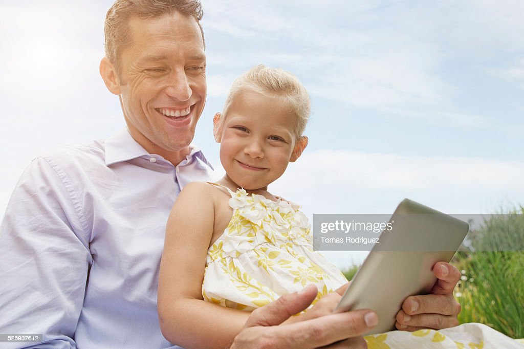 Father and daughter using digital tablet (4-5) outdoors : Foto de stock