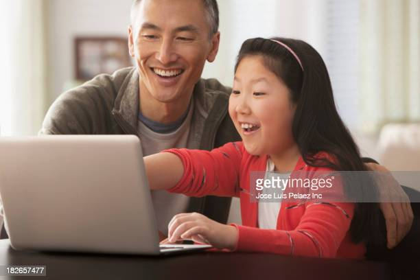 Father and daughter using laptop together