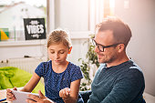 Father and daughter using tablet at home to finish homework