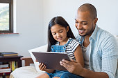 African father and smiling daughter sitting on sofa using digital tablet. Happy dad watching cartoon with his cute little girl. Cheerful father and daughter sitting on couch at home and playing with c