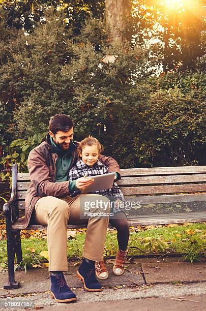 Vater und Tochter mit Tablet sitzen auf einer Bank
