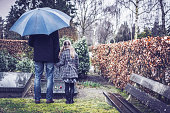 Father and daughter visiting gravestone of deceased mother with umbrella on rainy day
