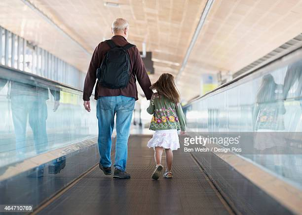 Father And Daughter Walk Down A Moving Pedway In The Malaga Airport