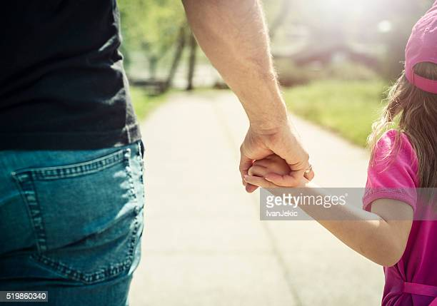 Father and daughter walking and holding hands in park