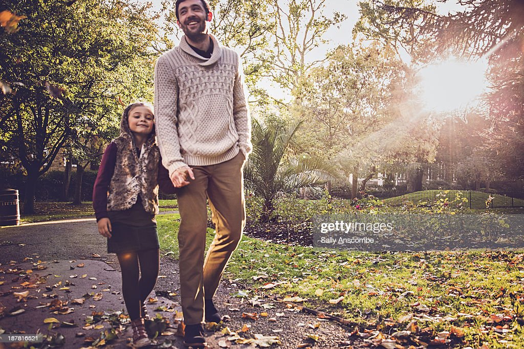 Father and daughter walking in the park together : Stock Photo