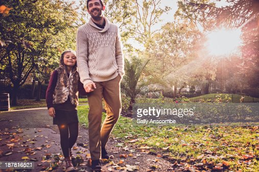 Father and daughter walking in the park together