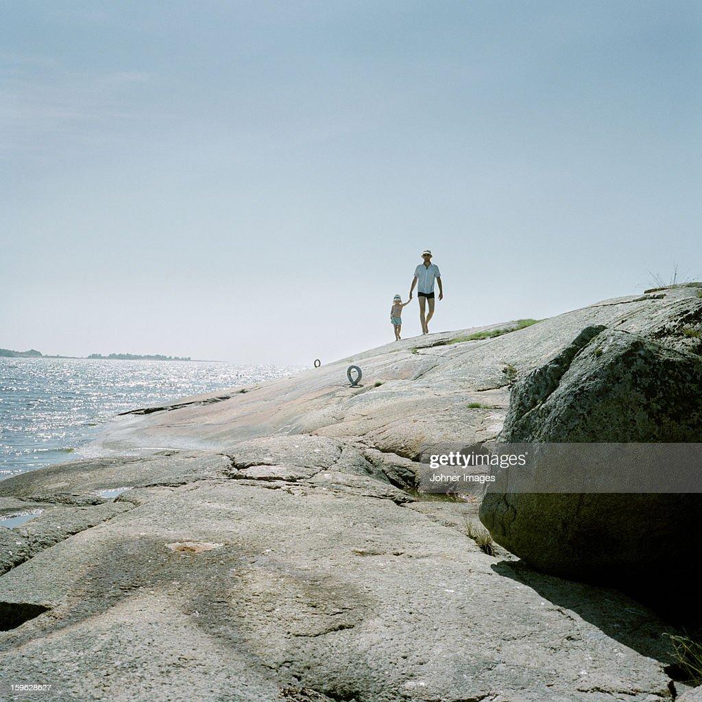 Father and daughter walking on cliffs, Blekinge, Sweden.