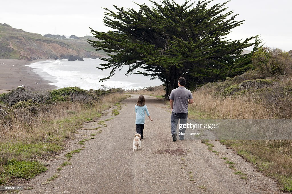 Father and daughter walking their dog : Stock Photo