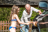 Father and Daughter Washing Family Car Together Outdoors