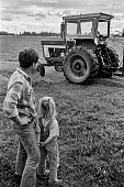 Father and daughter watch son work tractor