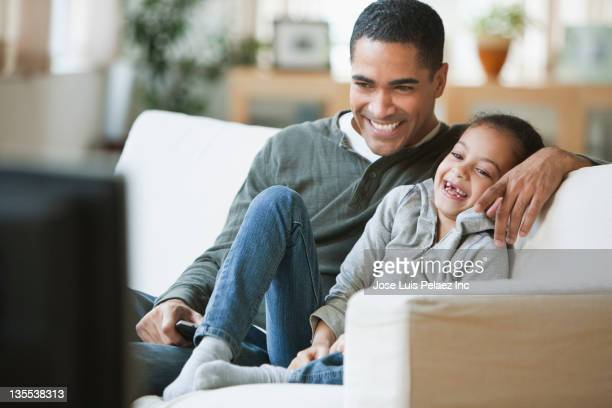 Father and daughter watching television together