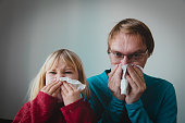 father and daughter wiping and blowing nose, family infection or allergy