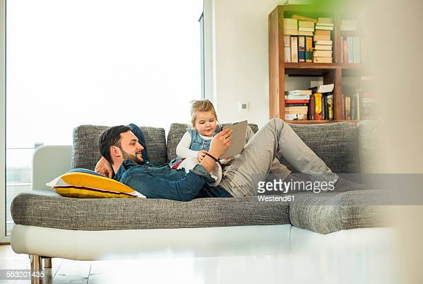 Father and daughter with digital tablet on sofa