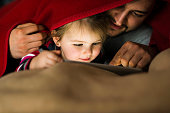 Father and daughter with digital tablet under blanket