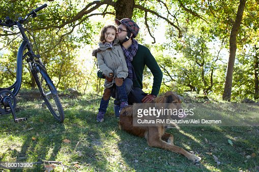 Father and daughter with dog in forest : Stock Photo