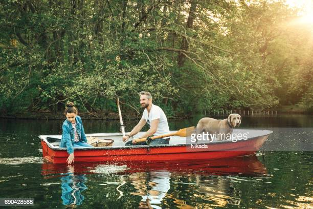 Father and daughter with dog in rowboat on lake