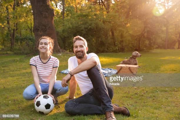 Vater und Tochter mit Hund ruht auf der Picknickdecke