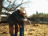 Father teaching daughter how to use lasso on ranch in Big Timber, Montana