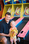 Father and daughter with tickets at arcade