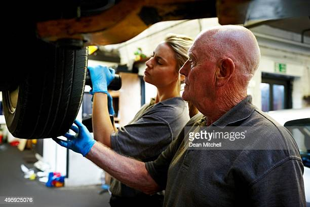 Father and daughter working together in automobile garage