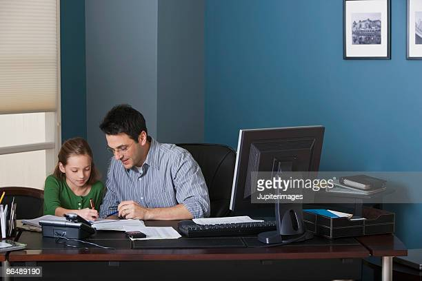 Father and daughter writing