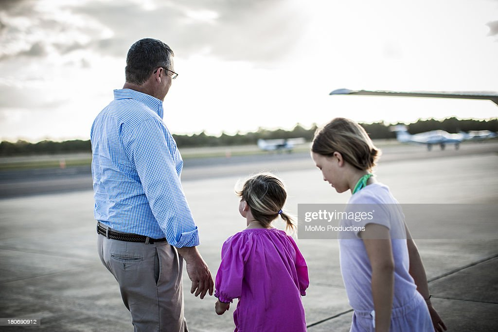 Father and daughters at airstrip : Stock Photo