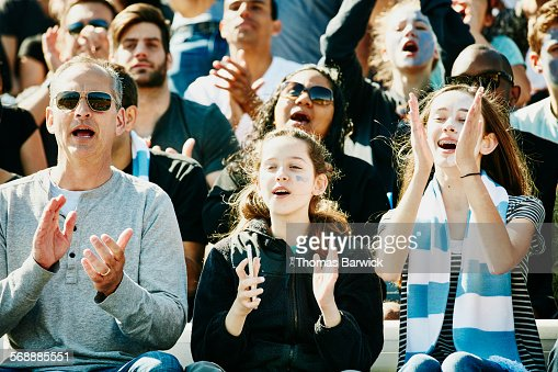 Father and daughters cheering at soccer match