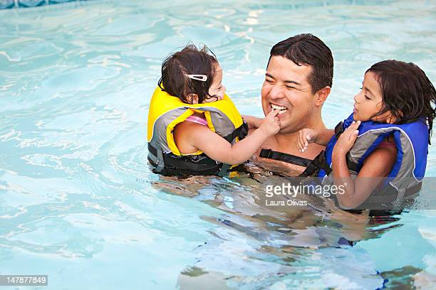 Father and daughters playful in swimming pool