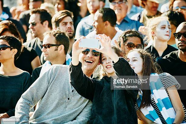 Father and daughters taking selfie in stadium