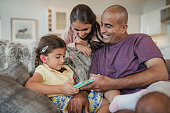 Father and his two daughters using and looking at the digital tablet and laughing.