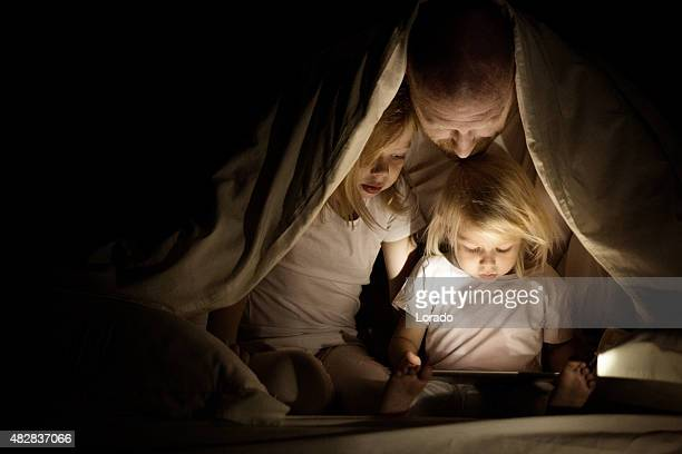 Father and daughters using a tablet device
