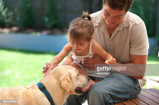 Father and excited daughter pat a dog