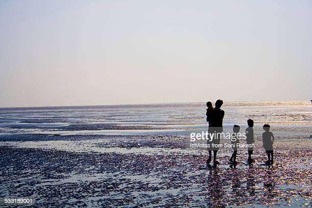 A father and four children standing on muddy beach