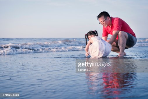 Father and girl playing on the beach : Stock Photo