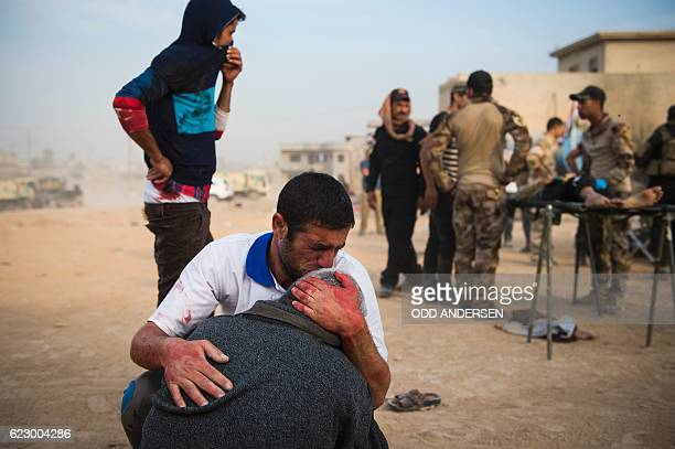 Father and grandfather of 15yearold Shafiq mourn as Iraqi forces surround his body at an outdoor field clinic in the Samah neighbourhood in Mosul on...